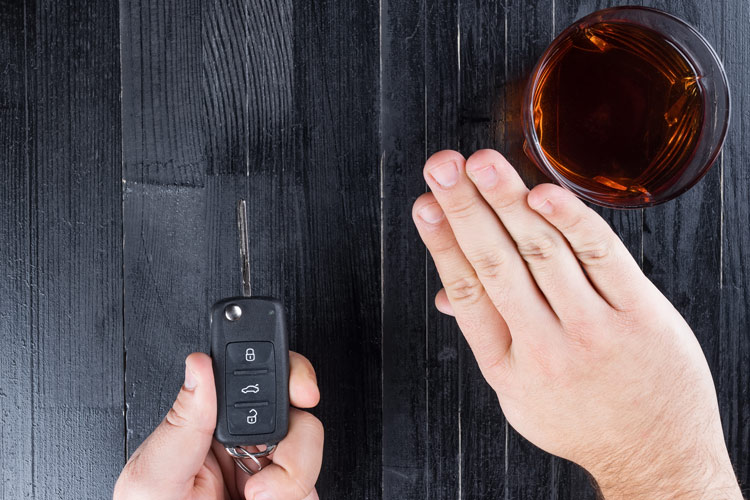 closeup of hand holding car key and refusing glass of liquor - harm reduction
