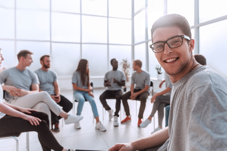 smiling young man sitting in circle with group - group therapy
