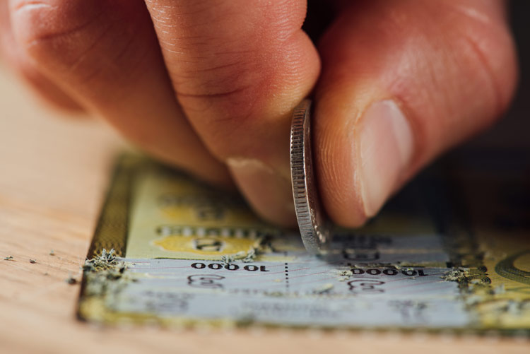 closeup of hand using coin to scratch a scratch off lottery ticket - substitute addiction