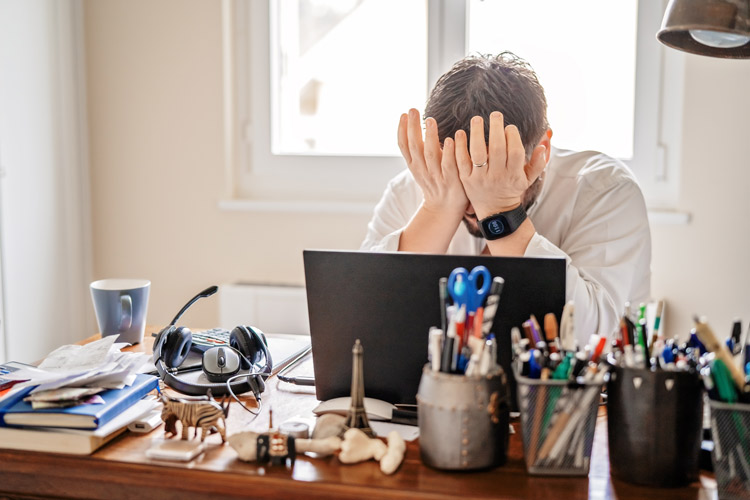 stressed man sitting at desk at home - substance use disorder