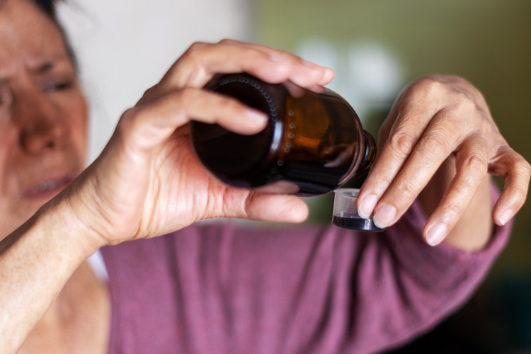 woman in her fifties pouring a dose of cough syrup - codeine