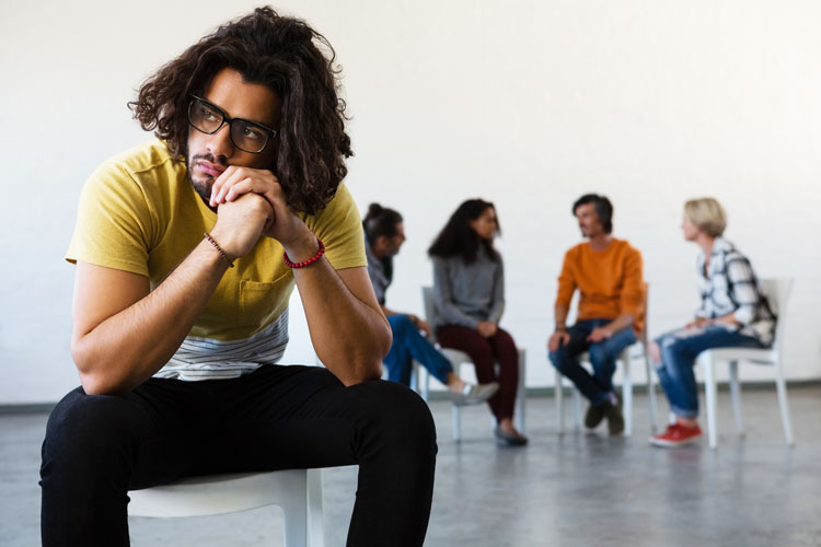 upset looking man outside of group circle at group therapy setting - anxiety and substance use