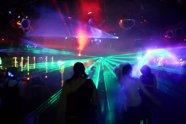 colored laser lights inside a rave or night club - club drugs